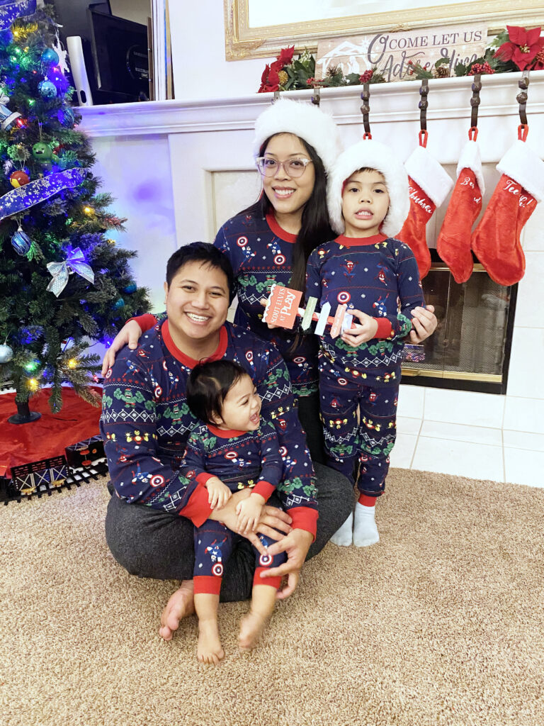 Family in holiday pajamas with fireplace and stockings behind them